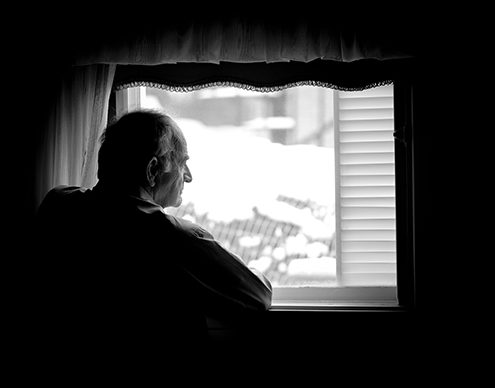 Lonely senior man looking at the window